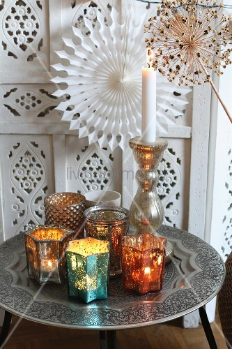 Colourful tealight holders and lit candles on Oriental tray table