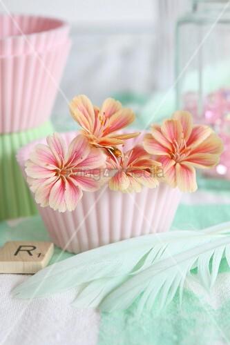 Pastellfarbene Blüten in rosa Silikonförmchen und türkise Federn in romantischem Ambiente