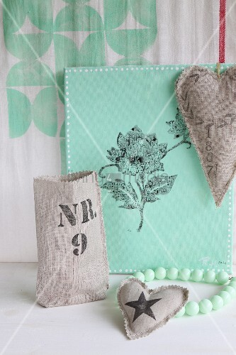 Hand-printed, heart-shaped linen cushions in front of mint-green canvas printed with floral motif