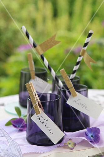 Place cards clipped to purple glasses with gold clothes pegs and drinking straws with washi-tape flags