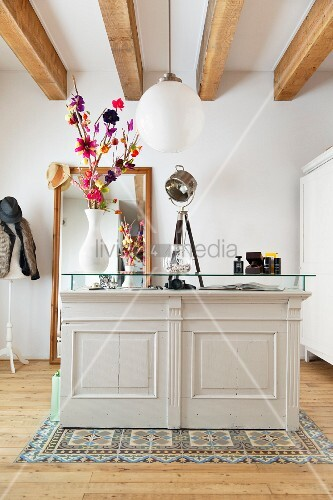 White-painted cabinet with glass top below pendant lamp with spherical lampshade hung from wood-beamed ceiling