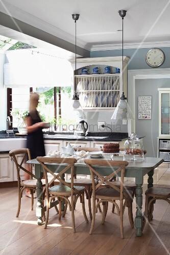 Rustikale Holzstühle mit Lehnenkreuz um Esstisch und Pendelleuchten in grosszügiger Landhausküche