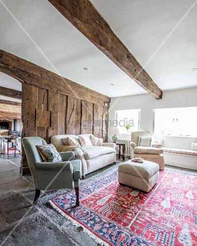Rustikales Wohnzimmer mit Holzbohlenwand im Hintergrund, davor Sofa ...