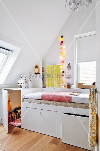 Custom-made white bed with storage drawers in teenager's bedroom with sloping ceiling