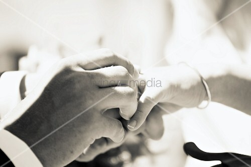 Man putting wedding ring on wife's finger