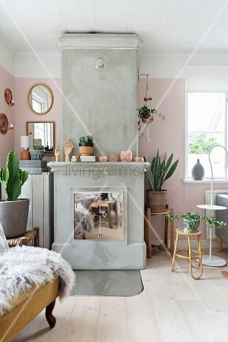 Kamin aus Beton mit verchromten Türen, Beistelltische mit Blumentöpfen vor rosa getönter Wand