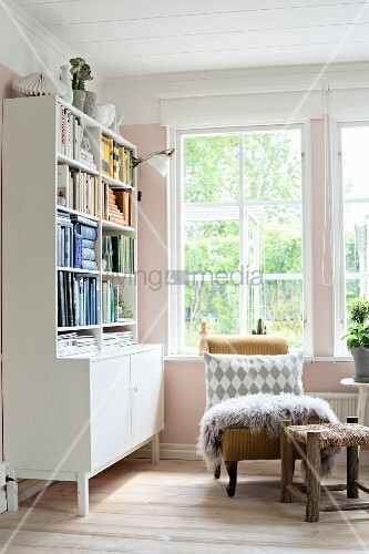 Patterned scatter cushion and fur rug on antique armchair below window and dresser with bookshelves in corner of room painted pink