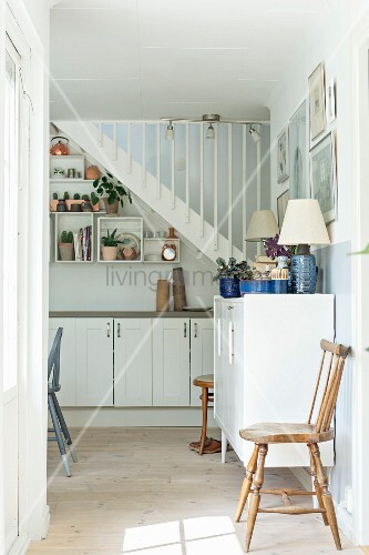 Rustic wooden chair against wall next to chest of drawers in kitchen-dining room; staircase above kitchen cabinets in background