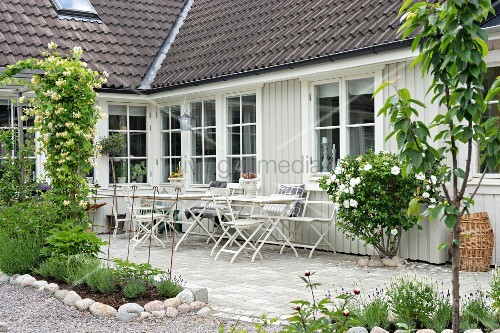 View from garden past flowerbeds and terrace to wooden house painted pale grey