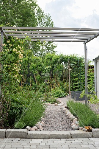 Simple wooden pergola over gravel garden path