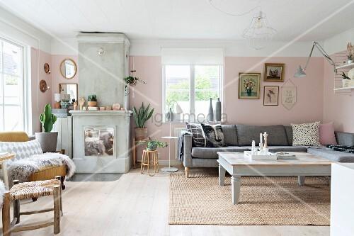 Gemütliches Wohnzimmer mit hellgrau lackierter Couchtisch und Polstersofa in Zimmerecke, seitlich Kamin aus Beton mit verchromten Türen an rosa getönter Wand