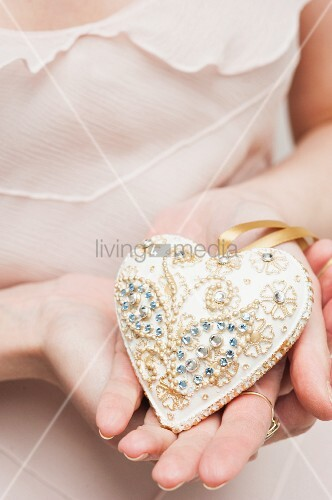 White, heart-shaped bauble with gilt ornamentation and rhinestones hald in woman's hands