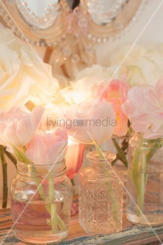 Delicate tulips in vases and jars on shelf and romantic mirror decorating feminine bathroom