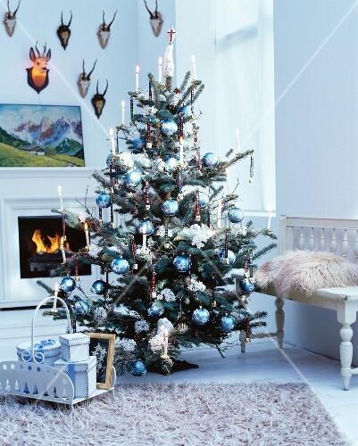 christbaum geschm ckt mit weissem baumschmuck und blauen kugeln in wohnzimmer mit kamin bild. Black Bedroom Furniture Sets. Home Design Ideas