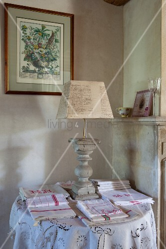 Table lamp with turned base amongst folded tea towels and tablecloths on side table in corner