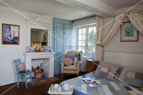 Double bed with patchwork quilt under draped fabric canopy and armchair below window in rustic bedroom