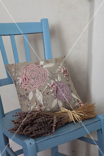Bunch of dried lavender and embroidered cushions on blue-painted kitchen chair