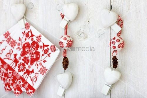 Festive arrangement of napkins, baubles, pine cones & love-hearts on wall