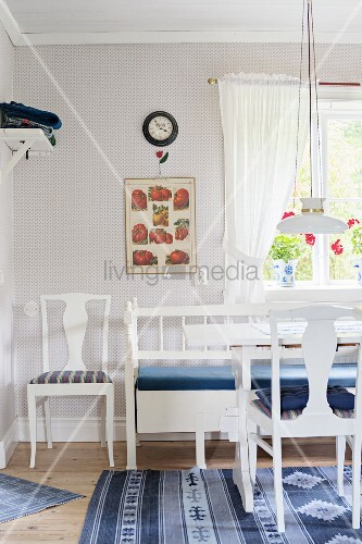 White-painted chairs and bench around table in front of window in rustic dining room