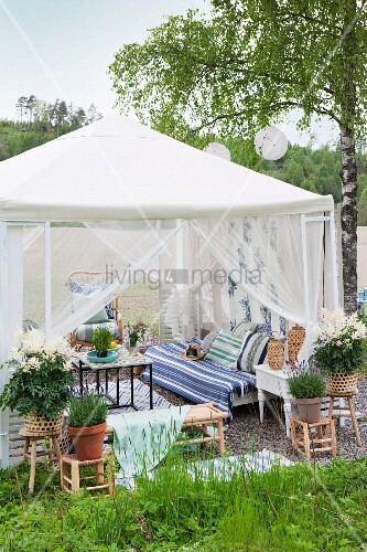 Romantic furnishings in garden pavilion with airy, draped curtains and potted plants