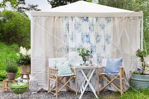 Table for two in front of romantic garden pavilion hung with airy fabric