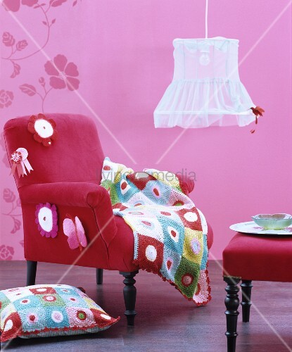 Pink interior with velvet armchair, footstool, crocheted accessories and vintage pendant lamp with fabric lampshade