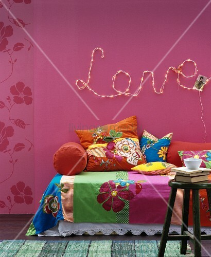 Floral Throws And Cushions On Sofa Below Motto U0027Loveu0027 Written In Fairy  Lights On Deep Pink Wall