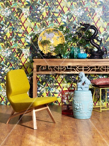 Yellow designer armchair and Chinese ornaments on console table against patterned wallpaper