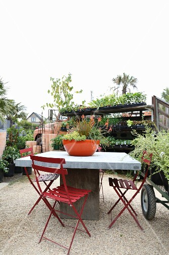 Table and red folding chairs on gravel floor in a garden center