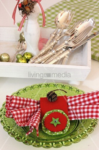 Hand-sewn, red napkin ring with pale green felt star and red and white gingham napkin on green glass plate