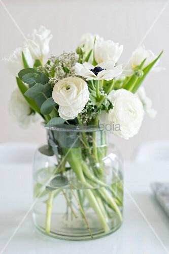 Glass vase of white spring flowers