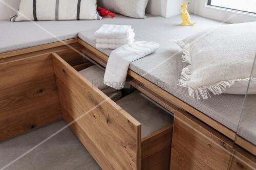 Maßgefertigte gepolsterte Holzeckbank mit Schubladen für Handtücher in Wellnessbad