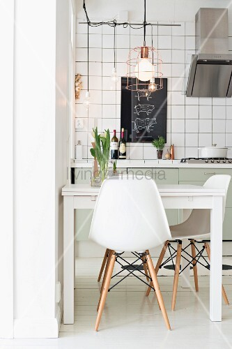 Classic white chairs around modern table below pendant lamp with wire lampshade in kitchen with white-tiled wall