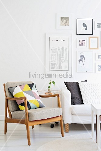 Fifties' armchair with wooden frame and retro cushion next to sofa below gallery of pictures on wall