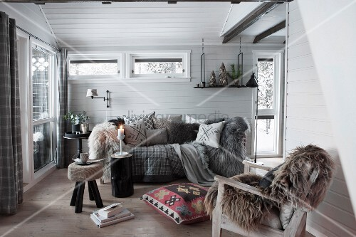 Fur rug on armchair and comfortable sofa in wood-clad interior