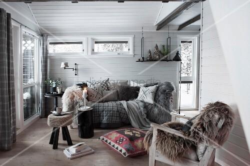 Sessel mit Tierfell und gemütliches Sofa in holzverschaltem Zimmer