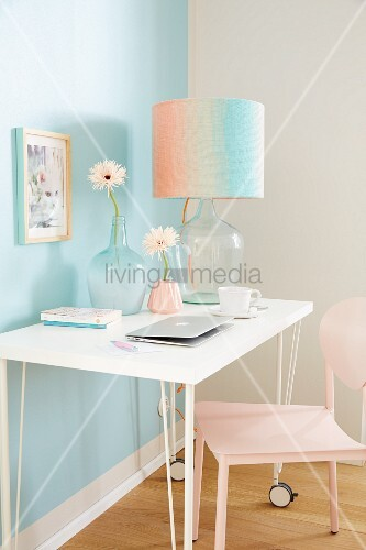 A knitted lamp shade with colour gradients on a white wall table