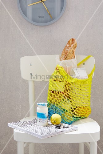 Selbst gehäkeltes Einkaufsnetz in Gelb auf weissem Küchenstuhl