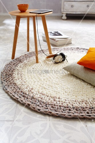 A homemade, round crocheted rug in brown tones