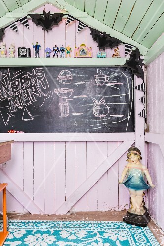 Chalkboard in pastel-coloured wooden play house
