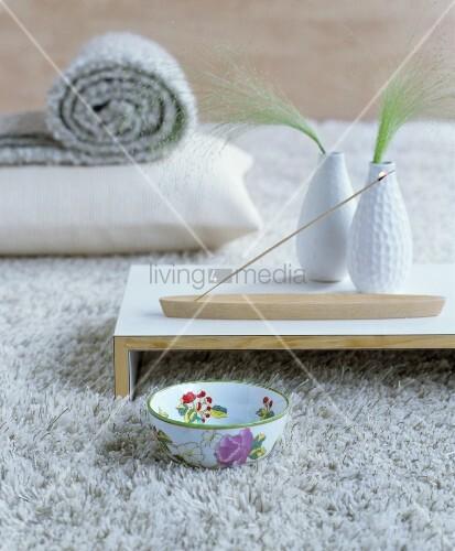 Lit joss stick on wooden tray on pale woollen rug