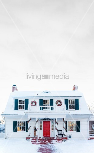 White, American country house with colourful shutters and Christmas decorations amongst snow