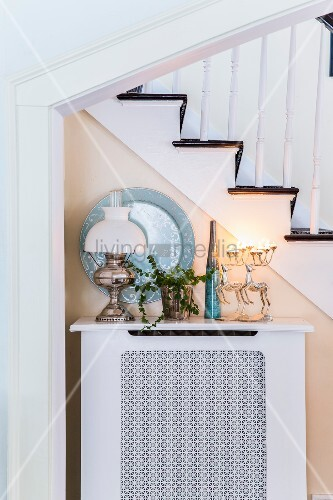 Stag-shaped candelabr and ceramic and classic oil lamps on top of radiator cover against side of staircase