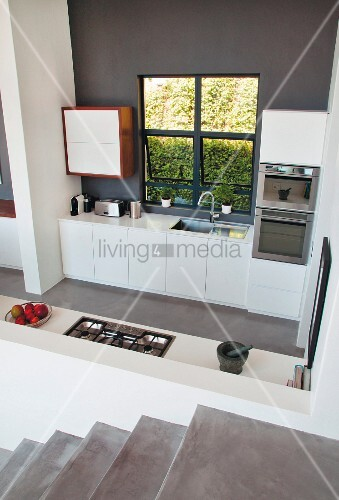 View across concrete staircase and down into open-plan kitchen with white cupboards on wall painted dark grey