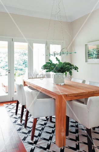 weisse armlehnst hle um massivholztisch auf schwarz wei gemustertemteppich in modernem. Black Bedroom Furniture Sets. Home Design Ideas