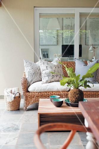 Comfortable veranda with modern coffee table and wicker sofa below window