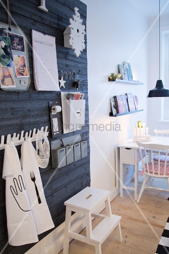Black board wall used as oversized pinboard; dining area with folding table in background