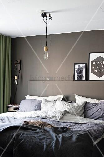 Gemütliches Doppelbett in modernem Schlafzimmer mit grau getönter Wand