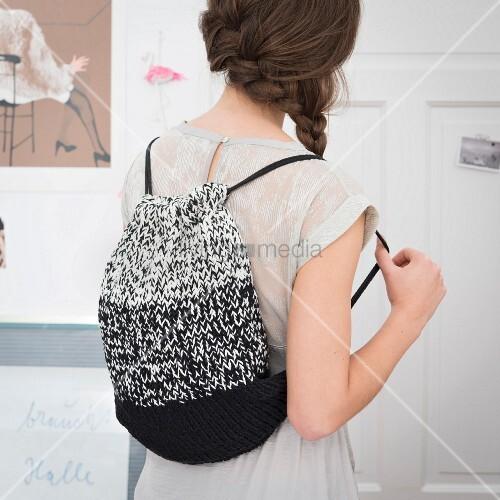 Stricken mit der Häkelnadel: Frau trägt geknookten Rucksack