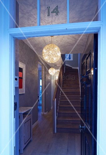 View through open front door into hallway with staircase and pattern of light and shade thrown by wicker lampshades